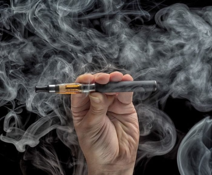 vape pen in vapour being held up by a man
